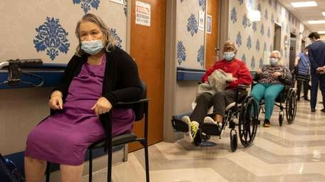 Nursing home residents wait on line to receive