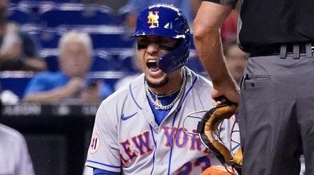 The Mets' Javier Baez, left, reacts after scoring