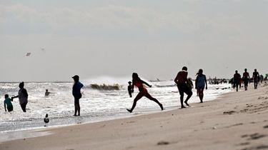 Beachgoers enjoy the waves and sand at Jones