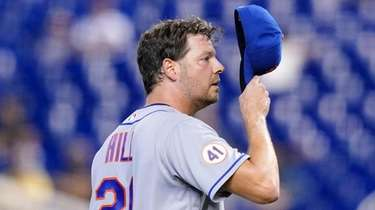 Mets starting pitcher Rich Hill adjusts his cap