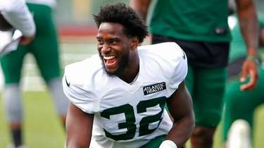 Jets running back Michael Carter stretches during training