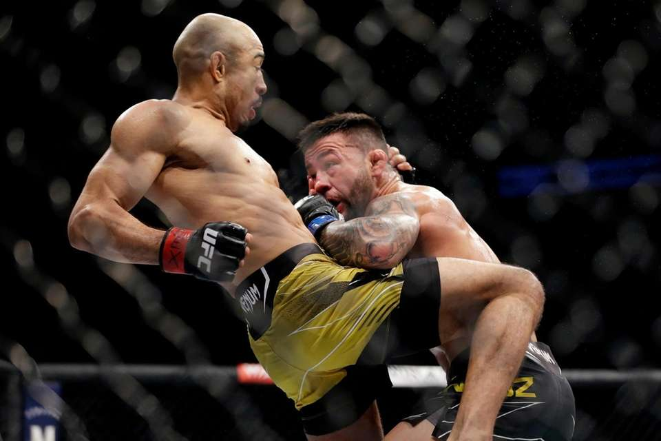 Jose Aldo, left, delivers a knee to the