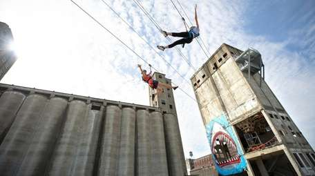 Two adventurers fly hight at the Buffalo RiverWorks.