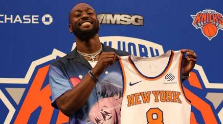 Kemba Walker of the Knicks holds up his