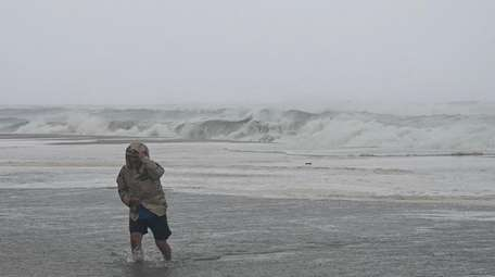 A man walks through the surf at Coopers
