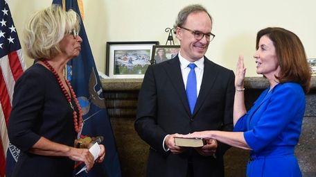 New York Chief Judge Janet DiFiore, left, swears