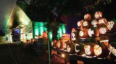 A pumpkin sculpture near a barn house at