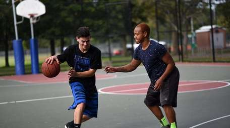 People play a game of basketball at Cantiague