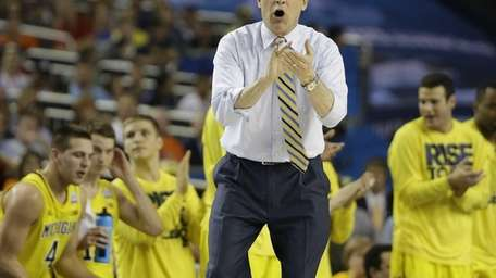 Michigan head coach John Beilein speaks to players