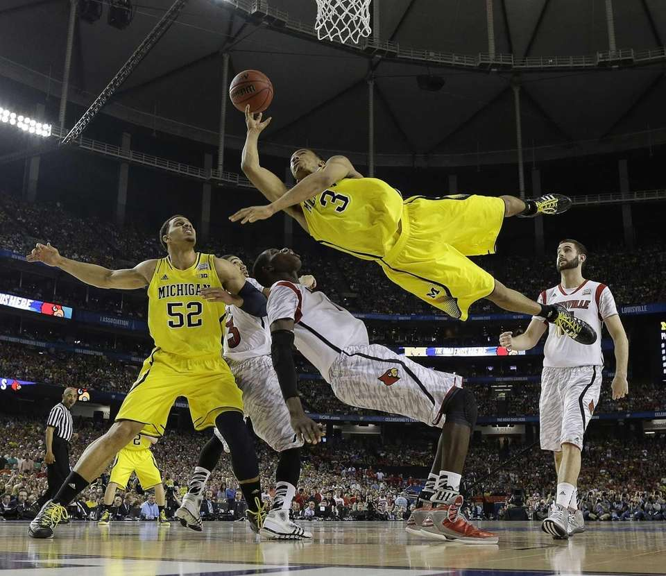 Michigan guard Trey Burke shoots over Louisville center
