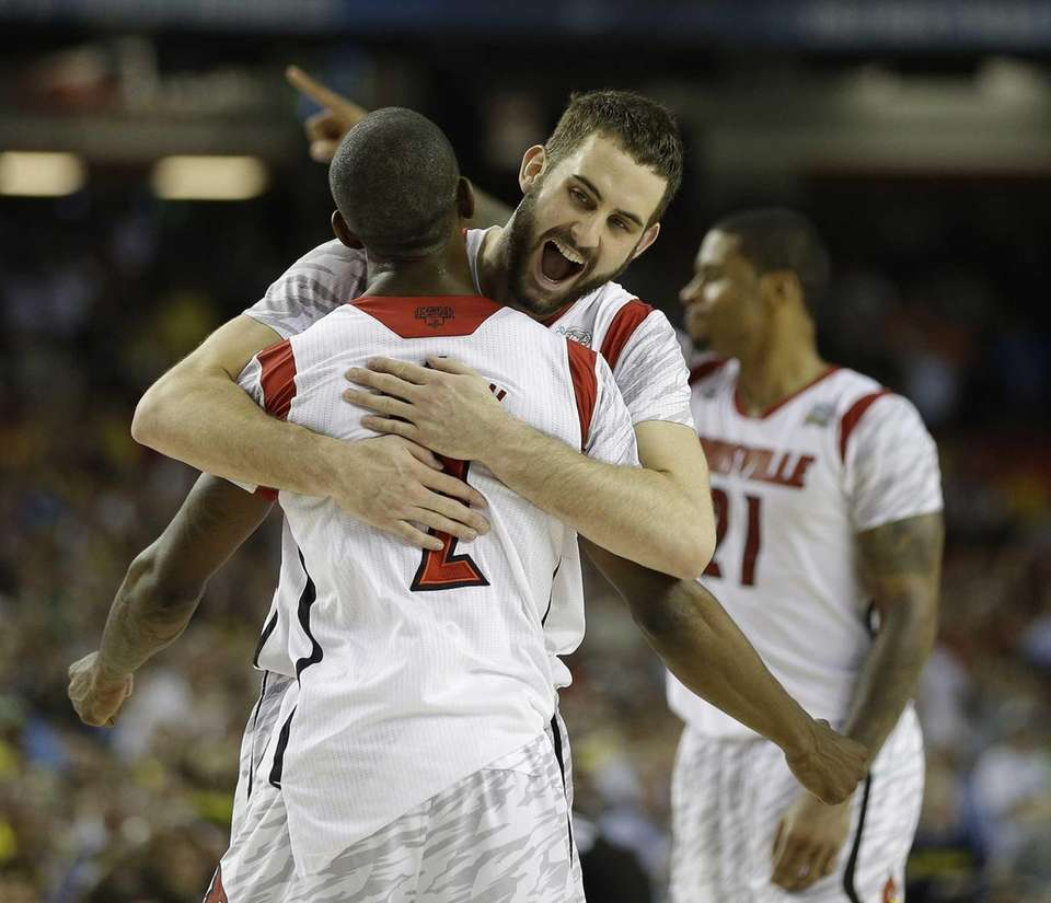 Louisville guard/forward Luke Hancock (11) embraces Louisville guard