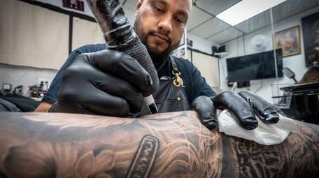 Shop owner Andy Rodriguez works on a customer