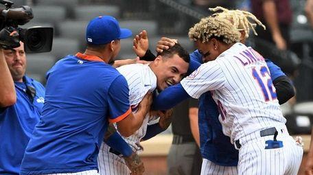 The Mets' Javier Baez is mobbed by Francisco