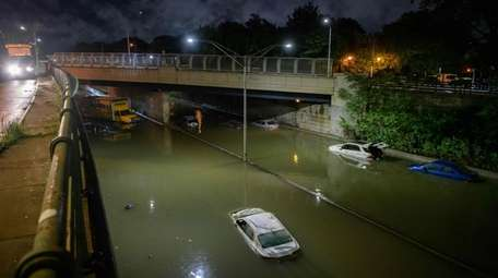 Floodwater surrounds vehicles following heavy rain on an