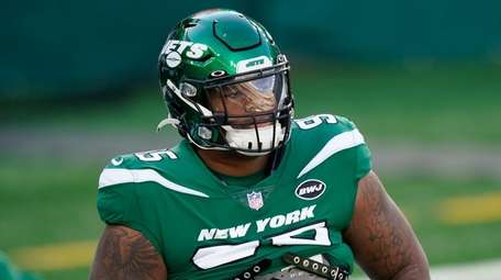 The Jets' Quinnen Williams warms up before a