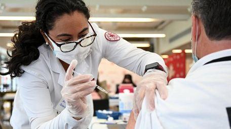 Nursing student Ana Quintanilla delivers the COVID-19 vaccine