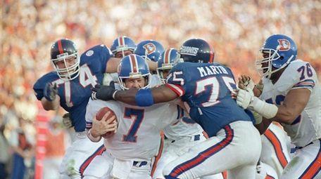 Broncos quarterback John Elway gets sacked for a