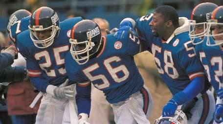 New York Giants linebacker Lawrence Taylor, center, is
