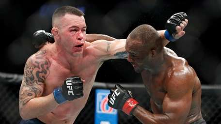 Kamaru Usman, right, fights Colby Covington in a