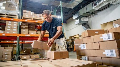 Warehouse associate Ivan Rosario places boxes onto pallets