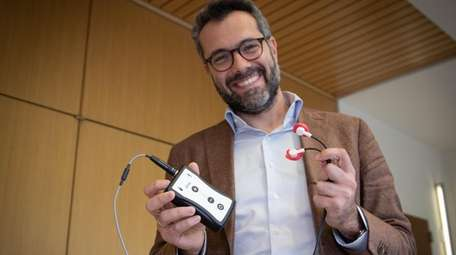 Feinstein Institutes researcher Theodoros Zanos holds a prototype