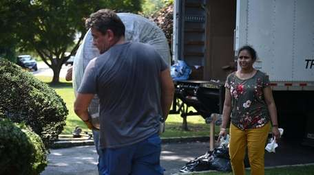 Movers unload the Rasaputras' furnishings at their new