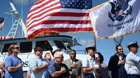 Captain James Schneider, left, holds a flag honoring