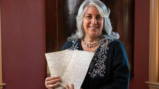 Claire Bellerjeau holds copies of pages from the