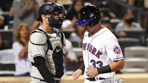 New York Mets catcher James McCann scores behind