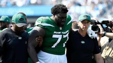 Mekhi Becton #77 of the Jets is helped