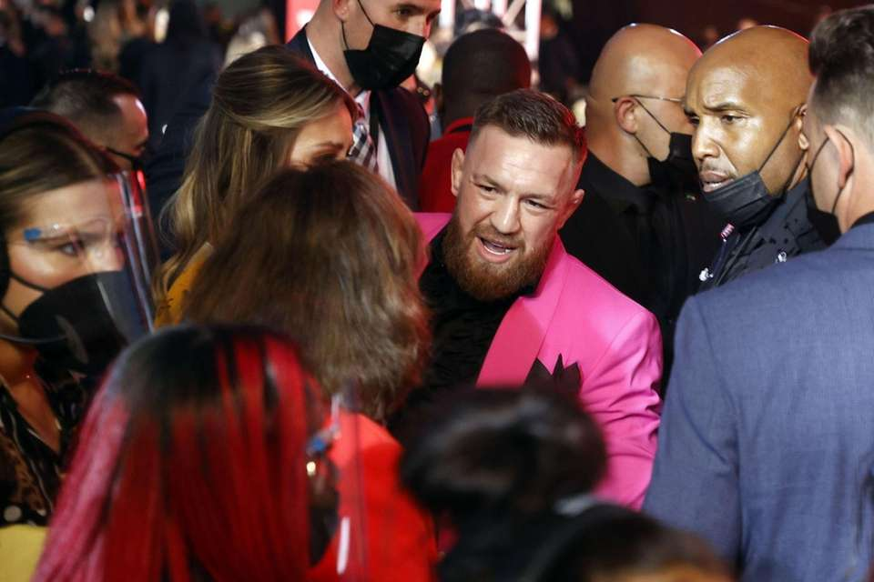 Conor McGregor (C) reacts while surrounded by security