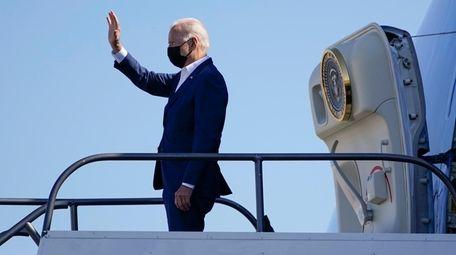 President Joe Biden waves as he boards Air