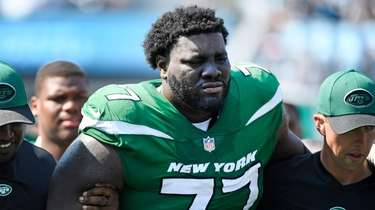 Mekhi Becton of the Jets is helped off