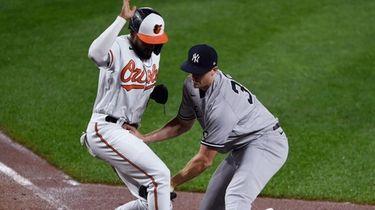 The Orioles' Kelvin Gutierrez scores the tying run