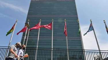 People walk past flags outside the United Nations