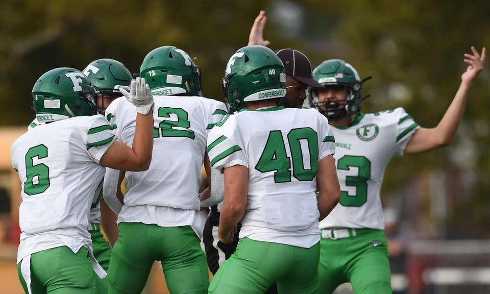 Farmingdale teammates react after an interception made by