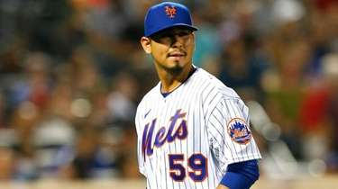 Mets starting pitcher Carlos Carrasco walks to the