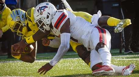 Oregon quarterback Anthony Brown scores as he is