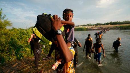 Migrants, many from Haiti, cross the Rio Grande