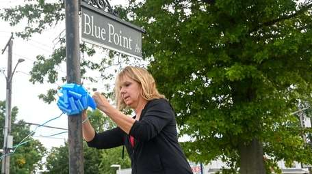Colleen Damiano, of Blue Point, ties a blue