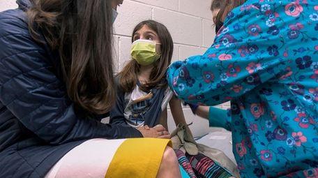 Alejandra Gerardo, 9, gets a shot during a