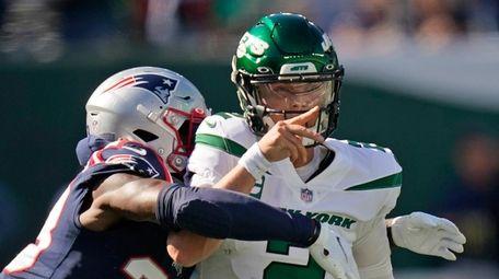 Jets quarterback Zach Wilson, right, throws under pressure