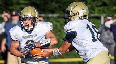 Bayport-Blue Point quarterback Brady Clark hands off to