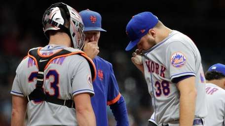 The Mets' Tylor Megill talks with pitching coach