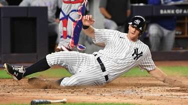 The Yankees' DJ LeMahieu slides to score as