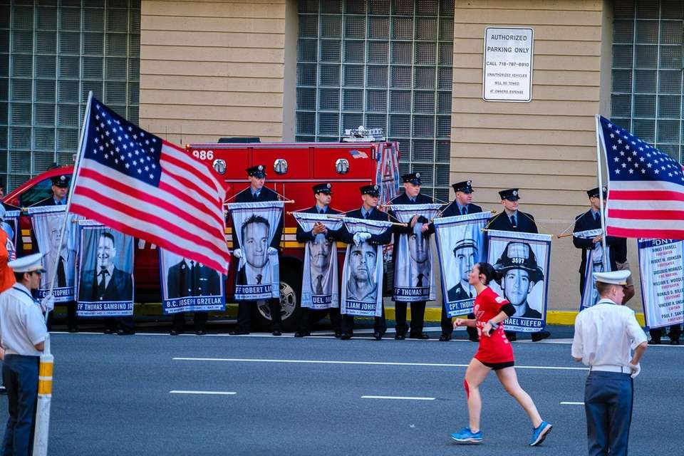 Runners pass portraits of the fallen as they