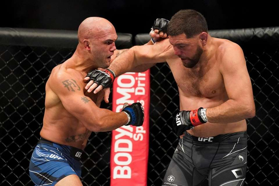 Robbie Lawler, left, throws a punch against Nick