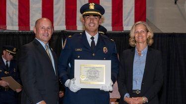 Nassau police Deputy Insp. Damian Ramos, center, with