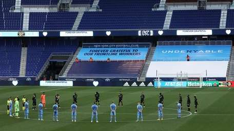 NYCFC and Columbus Crew stand during a moment