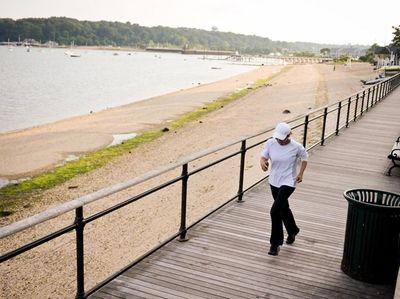 A woman runs on the boardwalk of Sea